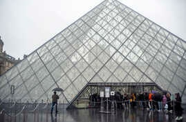 Tourists stand outside the Louvre museum, in Paris, France, March 1, 2020.