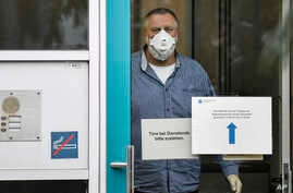 FILE - An employee with face mask and gloves waits for the next patient, behind the door of a coronavirus diagnostic center in Duesseldorf, Germany, March 2, 2020.