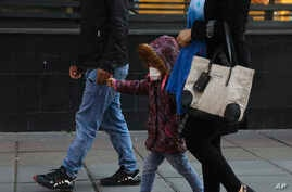A girl wears a mask while walking with her parents in downtown Tehran, Iran, Feb. 27, 2020. Iran on Thursday closed all schools due to the coronavirus outbreak.