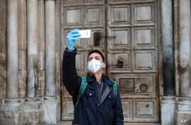 A man takes a selfie in front of the closed Church of the Holy Sepulchre, built in the location where Christians believe Jesus Christ was buried, in Jerusalem, March 25, 2020, as Israel tightens measures to fight the spread of the coronavirus.