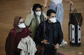 Passengers wearing masks arrive at the Ben Gurion Airport near Tel Aviv, Israel, March 10, 2020.