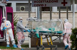 A patient in a biocontainment unit is carried on a stretcher from an ambulance arrived at the Columbus Covid 2 Hospital in Rome, March 17, 2020.