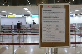 A Japan Airlines notice is displayed at Gimpo Airport in Seoul, South Korea, March 7, 2020.