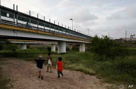 FILE - Migrant children walk with their families along the Rio Grande, as pedestrian commuters use the Puerta Mexico bridge to enter Brownsville, Texas, seen from Matamoros, Tamaulipas state, Mexico, June 26, 2019.