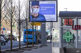 """An electronic billboard showing a doctor wearing a protective mask, with the words next to him reading """"Stay home; it will save a life,"""" is seen in a street in Moscow, Russia, March 25, 2020."""