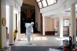 A man wearing protective suit and mask mops the floor inside the Hajjah Fatimah mosque, in Singapore, March 13, 2020.