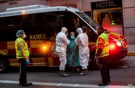 A patient, center, is transferred to a medicalized hotel during the COVID-19 outbreak in Madrid, Spain, March 24, 2020.