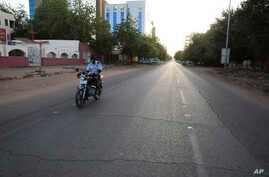 FILE - A lone motorcyclist is seen on an otherwise empty street in Khartoum , Sudan, March 24, 2020, as the Sudanese government ordered a nighttime curfew to prevent the spread of the coronavirus.