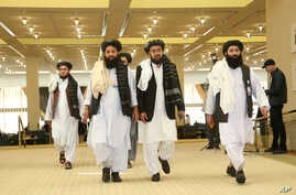 FILE - Members of Afghanistan's Taliban delegation arrive for the signing of an agreement between the Taliban and U.S. officials, in Doha, Qatar, Feb. 29, 2020.