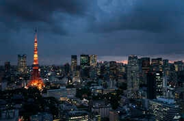 FILE- The Tokyo Tower is lit up at dusk as rain clouds hover over the city's skyline, in Tokyo, Japan, May 29, 2019.