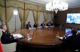 Turkish President Recep Tayyip Erdogan, left, flanked by his ministers and advisors participates in a teleconference with European leaders, in Istanbul, March 17, 2020.