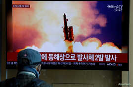 FILE - A man watches a TV broadcast showing a file photo for a news report on North Korea firing two unidentified projectiles, in Seoul, South Korea, March 2, 2020.