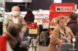 A shopper with an home made protective mask is seen in a Delhaize supermarket as it opens an hour earlier only for people above 65 years old in an attempt to protect the most vulnerable from coronavirus risks, in Brussels, Belgium, March 18, 2020.