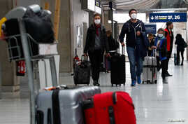 People wearing protective face masks arrive at Charles de Gaulle airport near Paris, France, as the coronavirus outbreak continues to expand, Feb. 29, 2020.