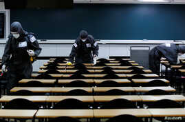South Korean soldiers clean desks with disinfectant in a classroom for civil service exams, following the rise in confirmed cases of coronavirus disease (COVID-19) in Daegu, March 15, 2020.