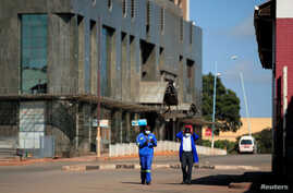 Men wearing protective masks walk down a deserted street on the first day of the 21-day nationwide lockdown aimed at limiting the spread of coronavirus disease (COVID-19) in Harare, Zimbabwe, March 30, 2020.