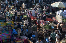Traders and customers gather to bargain prices of commodities at a crowded vegetable market