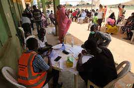 Health workers attend to people during a community COVID-19 coronavirus testing campaign in Abuja on April 15, 2020. - The…