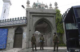 Policemen wearing facemasks stand guard outside a closed mosque during Friday prayers on a government-imposed nationwide…