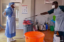A doctor of International Medical Corps (IMC) is disinfected at the isolation ward of Ministry of Health Infectious Disease…