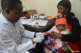 FILE - A doctor tests a child for malaria at the Ithani-Asheri Hospital in Arusha, Tanzania.