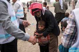 A displaced boy, who fled the violence in Mosul, receives a measles vaccination from a UNICEF-supported health worker in…