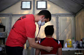 A medical staff of Global Response Management measures vital signs of a migrant patient at a migrant encampment where more than…