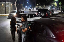 People stand close to their vehicles as they wait in line to fill up their vehicles with gasoline in Caracas, Venezuela.