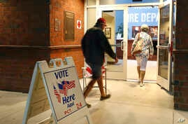 FILE - In this March 17, 2020, file photo voters walk into a polling station for the Florida presidential primary in Bonita.