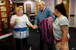 In this April 20, 2020, photo, nurses guide a resident at Wren Hall nursing home in the central England village of Selston.
