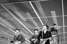 The Beatles are seen performing, date unknown.  From left to right:  Paul McCartney, George Harrison, John Lennon, and Ringo…