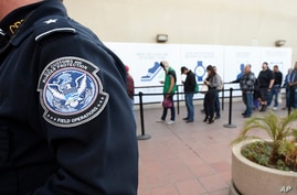 FILE - Pedestrians crossing from Mexico into the United States at the Otay Mesa Port of Entry