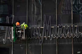 Workers install a sign for the Neiman Marcus department store at the Hudson Yards development in New York, March 8, 2019.