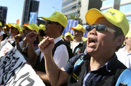 Taiwanese workers shout slogans during a protest in Taipei, Taiwan, Sunday, Jan. 4, 2020. Hundreds of workers from various…