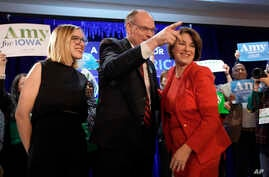 Democratic presidential candidate Sen. Amy Klobuchar, D-Minn., stands with her husband, John Bessler, and daughter Abigail.