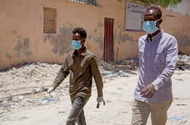 Somali men wear surgical masks on the street after after the government announced the closure of schools and universities and banned large gatherings, Mogadishu, March 18, 2020.