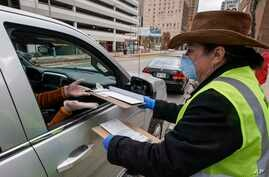 Jill Mickelson helps a drive up voter outside the Frank P. Zeidler Municipal Building Monday March 30, 2020, in Milwaukee.