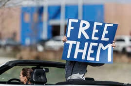 A protester wields a placard while riding in a convertible as members of the groups Abolish ICE Colorado, Sanctuary for All,…