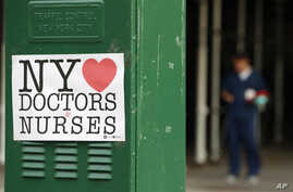 A sign acknowledging the work of doctors and nurses is posted on a traffic control box outside Brooklyn Hospital Center, as a hospital worker, right, waits for a traffic light to change before reporting to duty, Sunday, April 5, 2020, in New York.