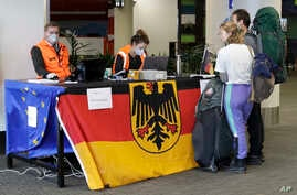 Foreign tourists wait to be checked by German Embassy staff at Christchurch Airport terminal as they prepare to check in for a charter flight back to Germany via Vancouver from Christchurch, New Zealand, Monday, April 6, 2020.