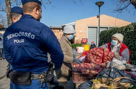 Police officers patrolling to control the observance of lockdown regulations introduced by the Hungarian government to contain the pandemic of coronavirus watch a customer buying vegetables at a market in the city centre of Szeged, Hungary, April 6, 2020.