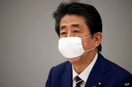 Japanese Prime Minister Shinzo Abe declares a state of emergency during a meeting of the task force against the coronavirus at the his official residence in Tokyo, Tuesday, April 7, 2020.