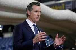 FILE — Gov. Gavin Newsom discusses the acquisition of the Sleep Train Arena for use as a field hospital, after touring the facility, in Sacramento, California, April 6, 2020.
