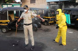 A civic worker sprays disinfectant on a policeman standing guard after a protest by migrant workers against the extension of…