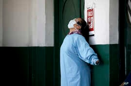 A worker at the Manuel Belgrano public hospital stretches outside the public hospital on the outskirts of Buenos Aires,…