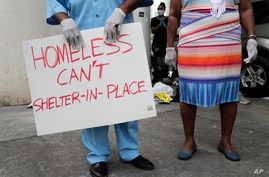 Anthony Swain stands with his wife Connie as he holds a sign advocating for safe housing for the homeless during a news conference by various community organizations, during the new coronavirus pandemic, April 17, 2020, in Miami.
