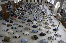 People attend evening prayers while maintaining a level of social distancing to help avoid the spread of the coronavirus