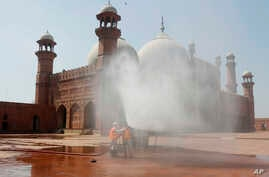 Volunteers disinfects the historical Badshahi Mosque ahead of the Muslim fasting month of Ramadan, in Lahore, Pakistan,…
