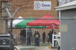 Tyson Fresh Meats plant employees line-up outside of the plant, Thursday, April 23, 2020, in Logansport, Ind.