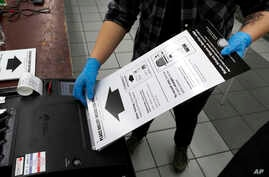 A poll worker at the Su Nueva Lavanderia polling place uses rubber gloves as she enters a ballot in the ballot box in Chicago, March 17, 2020.